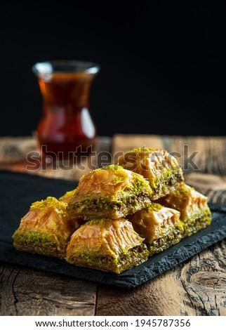 BAKLAVA. Traditional Turkish Desserts Baklava with Turkish Tea. Crispy pistachio baklava on black plate.