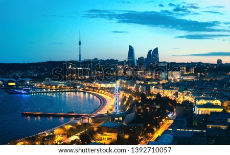 Baku at night. The capital city of Azerbaijan. Aerial panoramic cityscape view. Flame Towers, sea boulevard and street lights in the background.