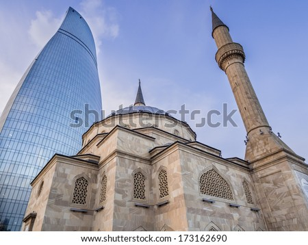 BAKU AZERBAIJAN NOVEMBER 22 2013 Sehidler Mescidi Mosque next to the Flame Towers in Baku Azerbaijan Flame Towers are the first flame-shaped skyscrapers in the world