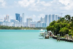 Bal Harbour, Miami Florida house dock with boat by light green turquoise ocean Biscayne Bay Intracoastal water and cityscape Sunny Isles Beach cityscape