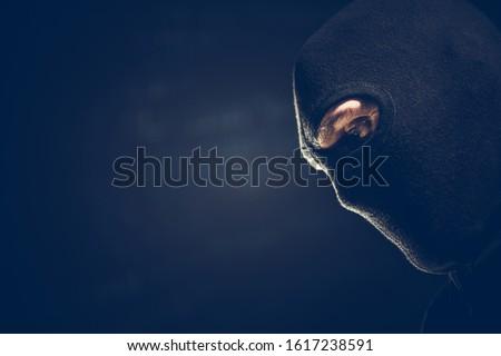 Balaclava Masked Robber Portrait. Caucasian Terrorist or Theft Wearing Black Face Mask. Left Side Copy Space. Dark Theme.