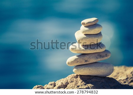 Balance and wellness retro spa concept, inspiration, zen-like and well being tranquil composition. Close-up of white pebbles stack over blue sea #278794832