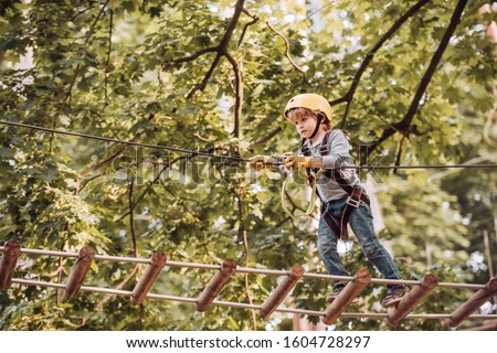 Photo of  Balance beam and rope bridges. Go Ape Adventure. Child concept. Climber child on training. Portrait of a beautiful kid on a rope park among trees. Carefree childhood.