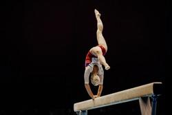 balance beam handstand female gymnast on black background