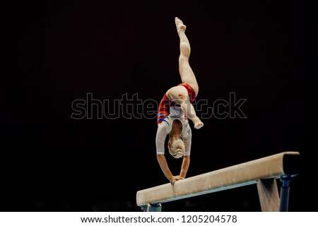 balance beam handstand female gymnast on black background #1205204578