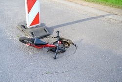 Balance bike (push bike) in pothole on asphalt street with detour alert traffic sign