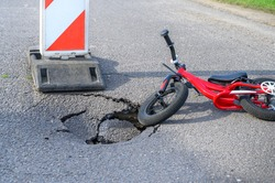 Balance bike (push bike) next to pothole on asphalt street with detour alert traffic sign