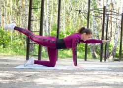 Balance exercise. Fit caucasian woman in magenta sportswear practice pilates outdoor in the sports ground, in summer, selective focus. Fitness, active morning, training, balance, healthy lifestyle.