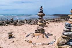 Balance of several stones of different sizes in stack in sand by the sea at  Farol beach in Milfontes, Vicentine Coast Natural Park PORTUGAL