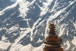Balance of stones. Balancing stones on the top of boulder. Balance of stones on the mountains background with a copy space. Stones balance, sustainability concept. Close up.