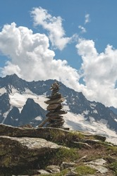 Balance of stones. Balancing stones on the top of boulder. Close up. Balance of stones on a blue sky and mountains background with a copy space. Stones balance, sustainability concept.