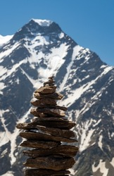 Balance of stones. Balancing stones on the top of boulder. Close up. Balance of stones on a blue sky and mountains background with a copy space. Stones balance, sustainability concept. Close up