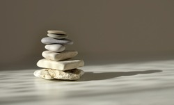 Balance pyramid stones on grey background, sunlight and shadows. Copy space.