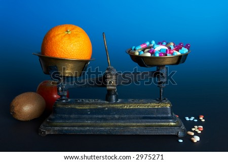 Balance weighing healthy food, fruit, and diet or vitamin pills