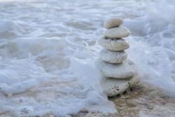 Balance zen stones pyramid on pebble beach with a splashing wave. Stability, balance, and harmony concept