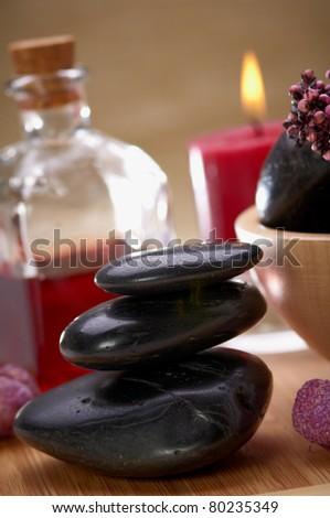 balanced black stones and essential oil