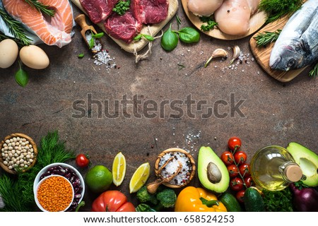 Balanced diet food background. Organic food for healthy nutrition. Meat fish beans and vegetables. Top view copy space on dark stone table.