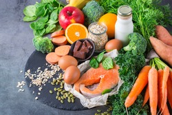 Balanced nutrition concept, asthma and respiratory relieving food, clean eating diet. Assortment of healthy ingredients rich in vitamin d, a, beta-carotene, magnesium for cooking on a kitchen table.