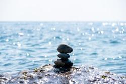 Balanced pebble pyramid on the beach on a sunny day. Abstract Sea bokeh on the background. Selective focus. Zen stones on the sea beach, meditation, spa, harmony, calmness, balance concept
