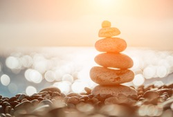 Balanced Pebbles Pyramid on the Beach on Sunny Day and Clear Sky at Sunset. Blue Sea on Background. Selective focus, Bokeh. Zen stones on sea beach, meditation, spa, harmony, calm, balance concept