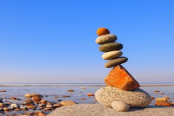 Balanced Rock Zen on the background of the sea. The concept of fall risk and unstable equilibrium