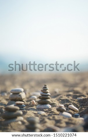 Balanced stone pyramid on pabbles beach with sunset. Zen rock, concept of balance and harmony. Calmness and pacification. Travel and beach vacations. Soft focus and beautiful bokeh. Sky.