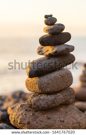 Balanced stone pyramide on shore of the ocean at dawn. Sea pebbles tower closeup symbolizing stability, zen, harmony, balance. Foto d'archivio ©