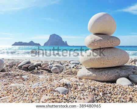Balanced stones on the beach of Cala d'Hort, Ibiza Island. View to the magic rock es Vedra in the background  Stok fotoğraf ©