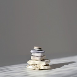 Balanced Zen stones on grey background, sunlight and shadows. Copy space, square image.