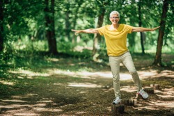 Balancing exercise outdoors. Mature woman standing on one leg, exercising balance