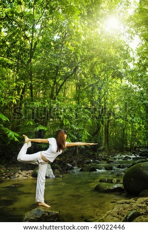 Balancing. Female practises balancing at  nature tropical forest in a morning.