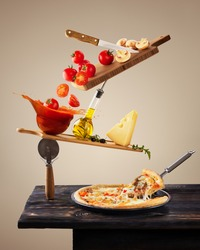 Balancing ingredients for making pizza. Levitation tomatoes. Conceptual food. Modern design. Contemporary art collage. Concept of fast food, breakfast, lunch.