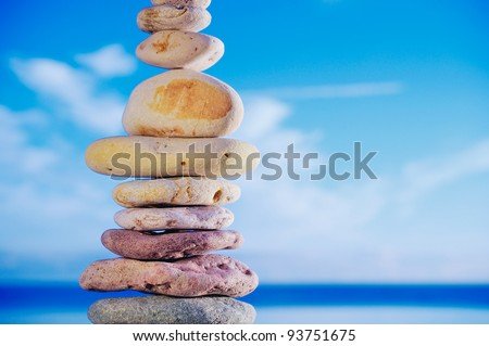 Balancing of pebbles each other on a sky background