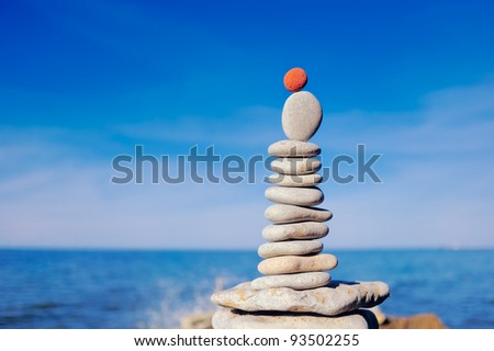 Balancing red stone on the top of pile of pebbles