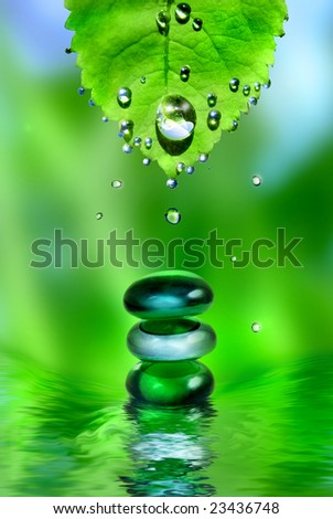 balancing spa shiny stones with leaf and water drops on green background