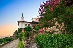 Balchik, Bulgaria / 06.08.2017: Balchik Palace Castle of Romanian Queen Marie at Bulgarian Black Sea coast. Beautiful romantic garden with colorful flowers.