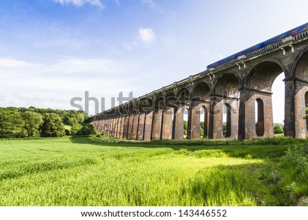 Balcombe Ouse Valley Viaduct designed by John Urpeth Rastrick for the London and Brighton Railway and completed in 1842 comprising 37 arches. Sussex England. Motion blurred train crossing at speed