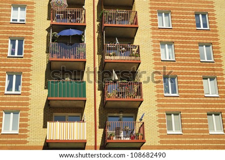 Balconies on the side of a building with many windows.