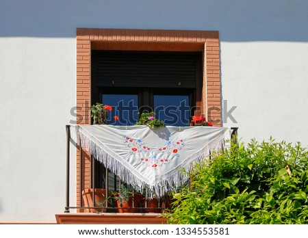 Balcony decorated with  Manila shawl and carnation and geraniums plants in clay pots, during the festivities of the Virgin Mary of Rocio, Almonte, Huelva, Spain, Europe