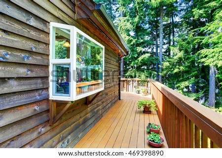 Balcony house exterior with wooden trim and flowers pots. Also wooden railings. Northwest, USA #469398890