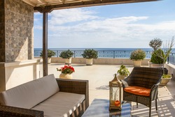 Balcony overlooking the sea. Relaxation area on a large modern terrace in a new building on the first line with panoramic sea views.  Luxury vacation rental. Overseas property on the sea coast.