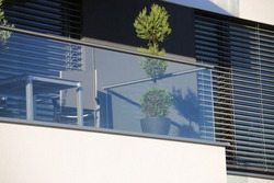 Balcony railings made of glass and stainless steel, behind them windows with modern blinds