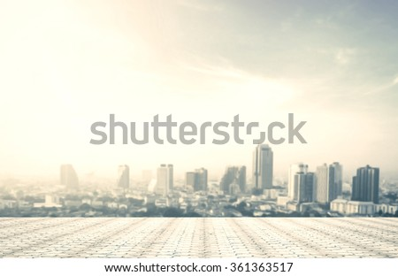 Balcony view at rooftop with stone floor and abstract blurred building skyline background.