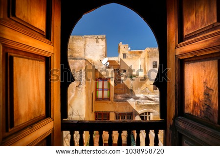 Balcony view of Arab building and window. Rustic balcony doors and view in the Medina of Fes, Morocco. Famous example of Moroccan architecture and a popular tourist sight #1038958720