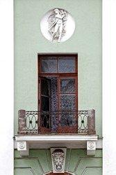 Balcony with a cast-iron fence and stucco molding, with an open balcony door against the background of a green wall with a bas-relief in a round niche.
