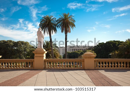 balcony with a statue on a background of palm trees and blue sky