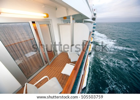 balcony with chairs table lamp on ship with view on sea