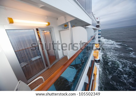 balcony with chairs table lamp on ship with view on sea in evening