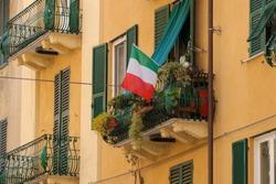 Balcony with flowers and Italian flag, house facade, Italy
