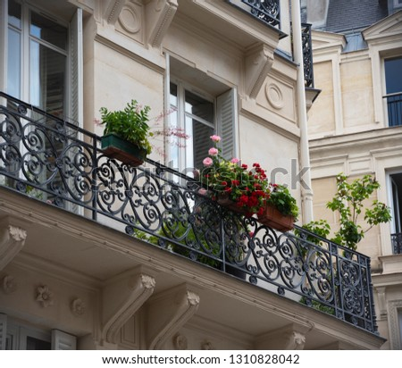 Balcony with forging railing decorated with roses and geranium flowers.Typical Parisian architecture. Building architecture detail. Spring/summer vacation in Paris. Europe destination, city break. #1310828042